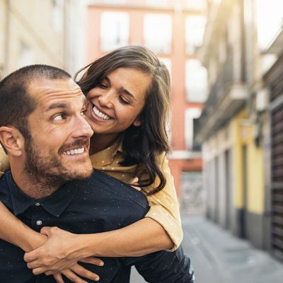 A young couple outside on vacation smiling with each other.