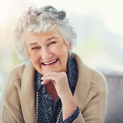 An older woman smiling with her chin resting on her hand.