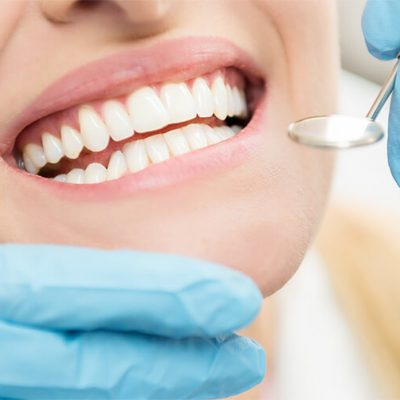 A close up of a patient's smile while the dentist checks their mouth.