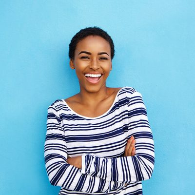 A young woman smiling bright in front of a blue background.