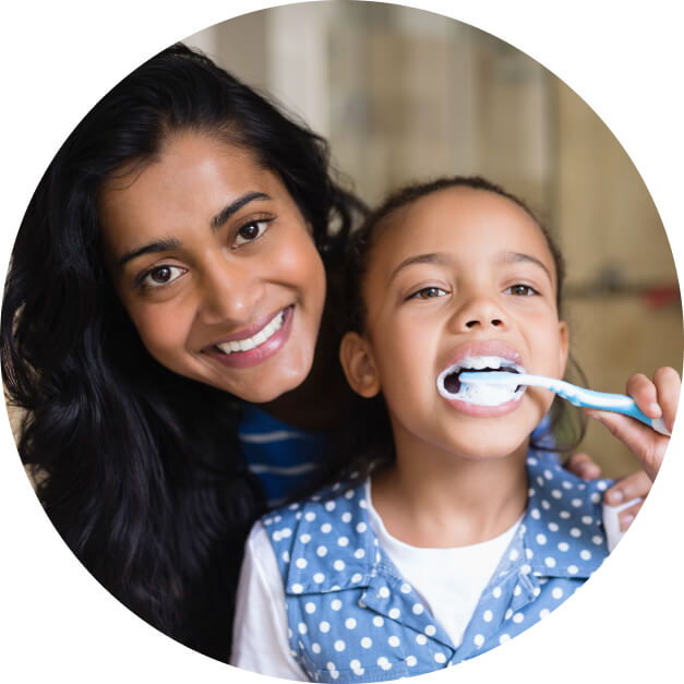 A mother showing her daughter how to brush her teeth.