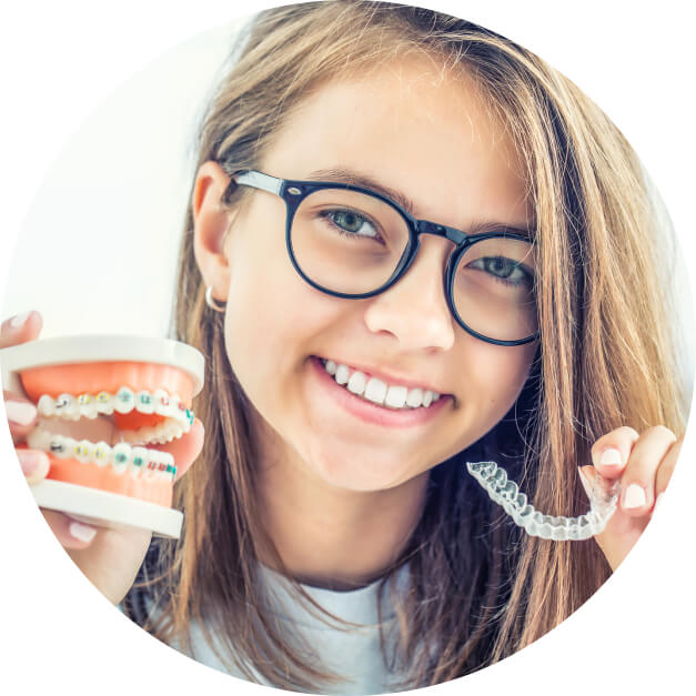 A young girl holding up Invisalign aligner versus traditional braces model.