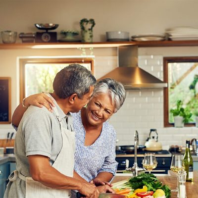 An older couple smiling as they cook dinner together.