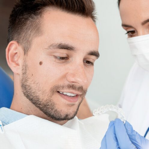 A young patient looking at Invisalign aligners as a treatment option.