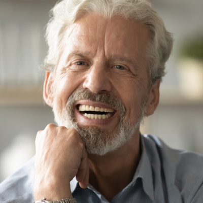 An older man smiling with his chin resting on his hand.