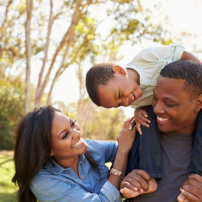 A family of three outside having fun and laughing together.