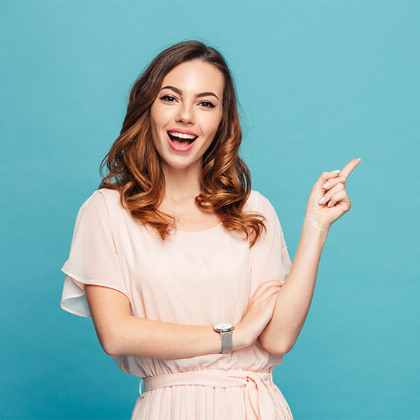 A young woman smiling and pointing her finger up in front of a blue background.